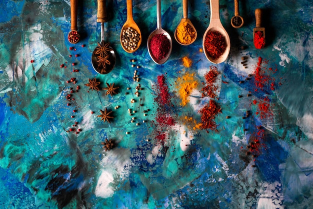 Verschiedene gewürzlöffel auf blauem betontisch.