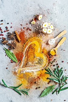 Verschiedene gewürzpulver paprika curry koriander ingwer getrocknete zwiebeln und knoblauch kurkuma zimt pfeffer anis und kräuter auf grauem hintergrund indische und asiatische küche liebe zu gewürzen