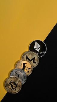 Verschiedene glänzende kryptowährungsmünzen. bitcoin, litecoin, ethereum, monero und neo auf gelbem und schwarzem vertikalem hintergrund mit kopienraum.