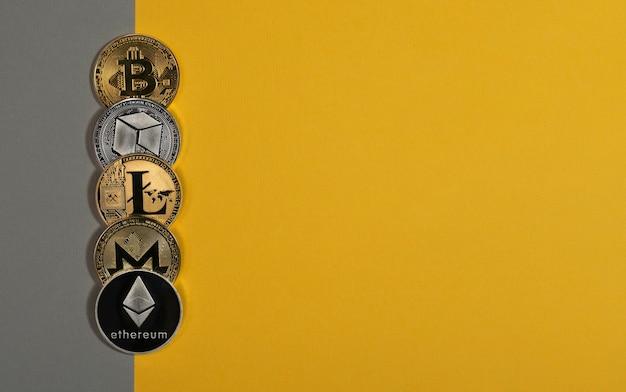 Verschiedene glänzende kryptowährungsmünzen, kryptowährung. bitcoin, litecoin, eth, monero und neo auf gelbem und grauem hintergrund. banner mit kopienraum für text.