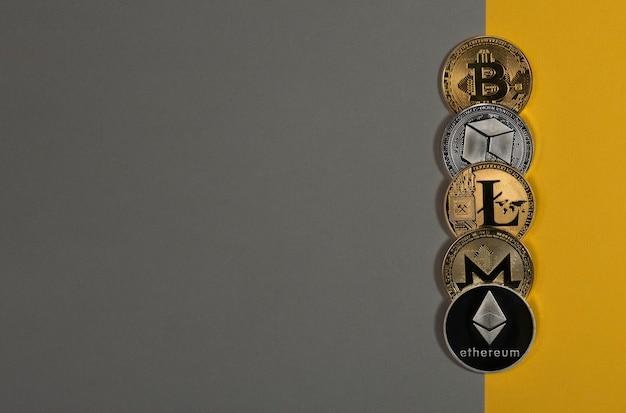 Verschiedene glänzende kryptowährungsmünzen, kryptowährung. bitcoin, litecoin, ethereum, monero und neo auf gelbem und grauem hintergrund. banner mit kopienraum.