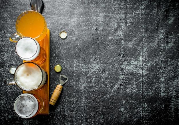 Verschiedene gläser bier auf einem hölzernen schneidebrett mit öffner auf schwarzem rustikalem tisch