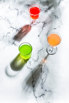 Verschiedene gläser mit hellen farbgetränken, in direktem hartem licht, langen schatten und marmorhintergrund