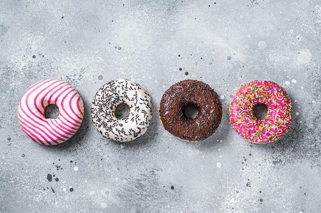 Verschiedene glasierte donuts auf einem küchentisch. grauer hintergrund. ansicht von oben.