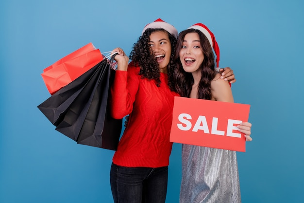 Verschiedene glückliche frauen mit bunten einkaufstaschen und rotem copyspace verkaufszeichen getrennt über blau