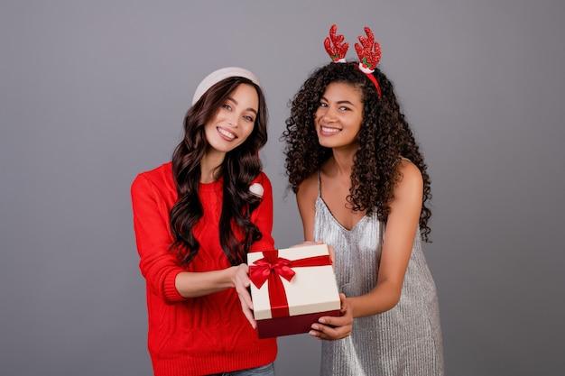 Verschiedene glückliche frauen mit geschenkbox mit dem tragenden weihnachtshut des bandes lokalisiert über grau