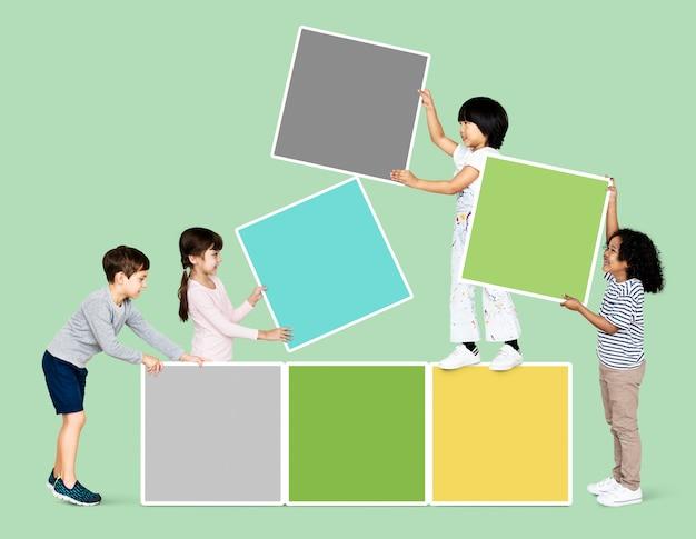 Verschiedene glückliche kinder, die leere quadratische bretter stapeln