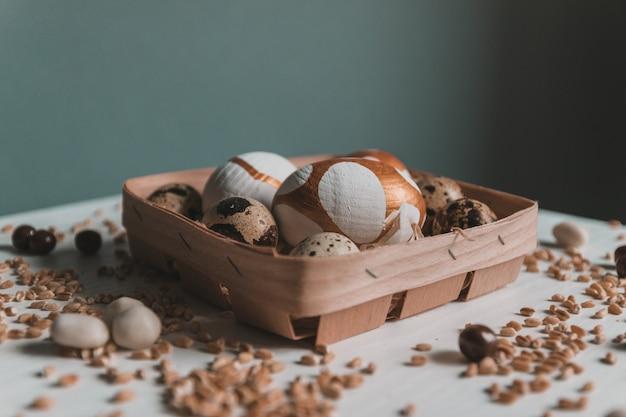 Verschiedene goldene ostereier, schokoladen-dragee-bonbons und hirse in einem korb auf grüner wand