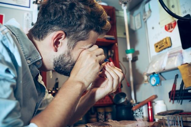 Verschiedene goldschmiedewerkzeuge am schmuckarbeitsplatz. juwelier bei der arbeit in schmuck.
