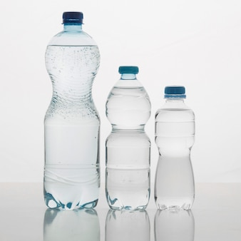 Verschiedene größen von flaschen mit wasser vorderansicht gefüllt