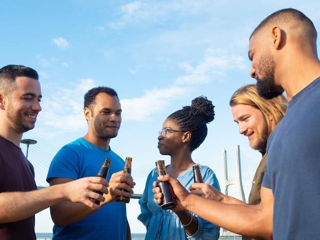 Verschiedene gruppe freunde, die draußen bier trinken
