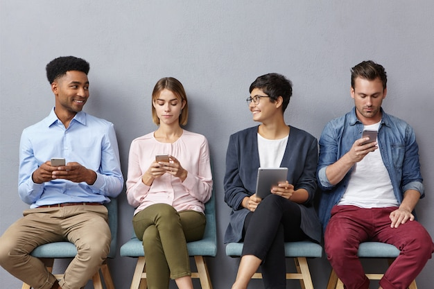 Verschiedene gruppen junger menschen führen lebhafte gespräche, indem sie in der warteschlange sitzen und moderne geräte für verschiedene ziele verwenden