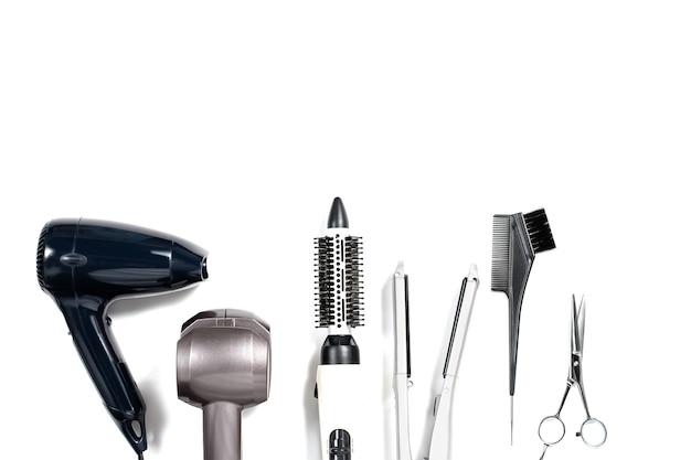 Verschiedene haarstyling-tools auf weißem hintergrund, draufsicht, kopierraum