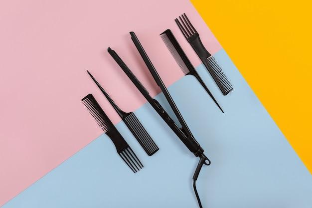 Verschiedene haarstylinggeräte auf blauem, gelbem, rosafarbenem papierhintergrund, draufsicht. platz kopieren. stillleben. attrappe, lehrmodell, simulation. flach legen