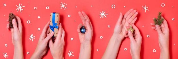 Verschiedene hände, die roten fahnenhintergrund der weihnachtselemente halten