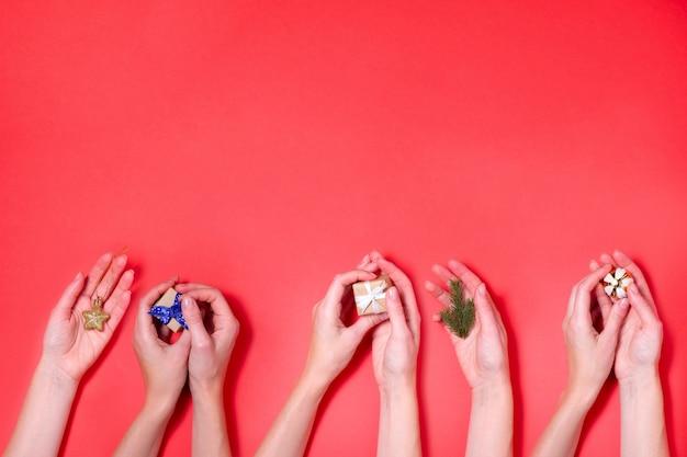 Verschiedene hände, die weihnachtselement-rothintergrund halten
