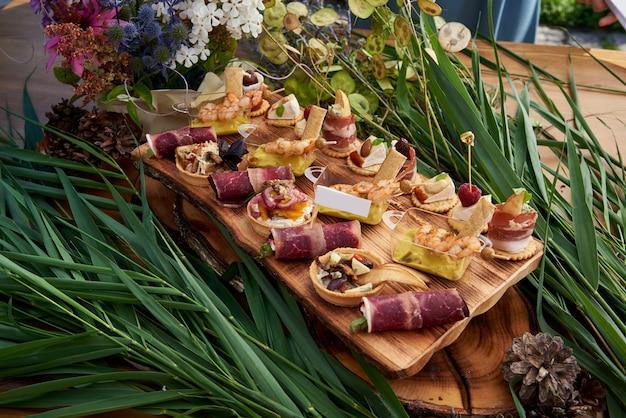 Verschiedene häppchen mit räucherlachs, gurke, tomaten, käse, fleisch. frühstücksbuffet mit verschiedenen snacks. buffet tisch mit snacks, obst, canape, süßigkeiten und vorspeisen.