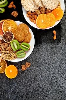 Verschiedene hafer-müsliriegel, reiscrips, mandeln, kiwis und getrocknete orangen