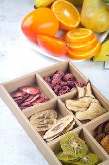 Verschiedene handgemachte getrocknete chips im karton auf grauem hintergrund. gesundes ernährungskonzept, snack, kein zucker. pflegepaket vorbereiten, saisonale geschenkbox. umweltfreundlicher korb für thanksgiving, weihnachten,