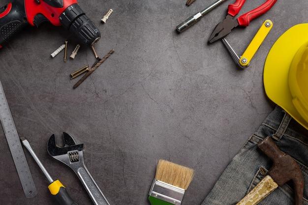 Verschiedene handliche werkzeuge auf dunklem hintergrund, hintergrundkonzept des arbeitstages