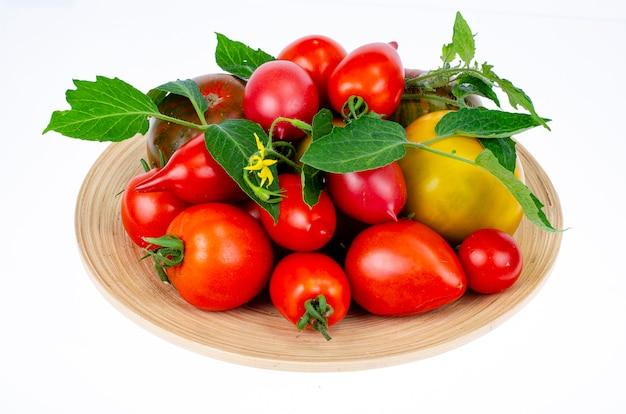 Verschiedene hausgemachte bunte tomaten in verschiedenen formen auf holzplatte. studiofoto.