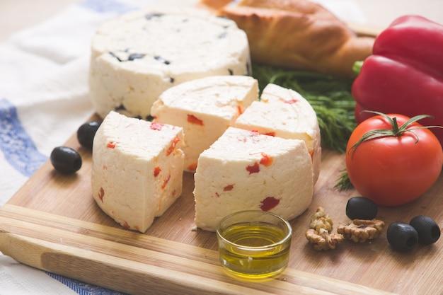 Verschiedene hausgemachte käse und paprika und kräuter olivenöl oliven und brot auf einem holzbrett