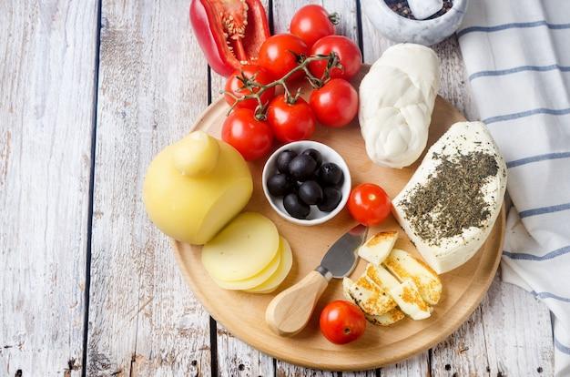 Verschiedene hausgemachte käsige pasta filata, provolone in verschiedenen formen und größen auf holzuntergrund, suluguni, zopf, caciocavallo, halloumi mit tomaten, pfeffer, oliven, trauben, feigen und kräutern