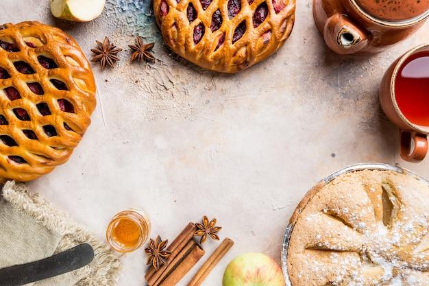 Verschiedene hausgemachte kuchen mit zutaten. crostata offene beerenpastete und apfelkuchen auf einem tisch von oben
