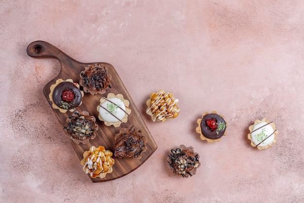 Verschiedene hausgemachte mini-törtchen mit nüssen und schokoladencreme.