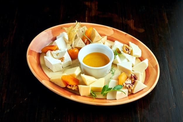 Verschiedene hausgemachte ukrainische käsesorten: bryndza, ziegenkäse, hartkäse, serviert auf einem teller mit honig.