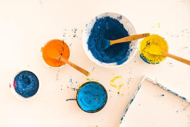 Verschiedene helle trockene farben in kleinen schüsseln in der nähe des rahmens