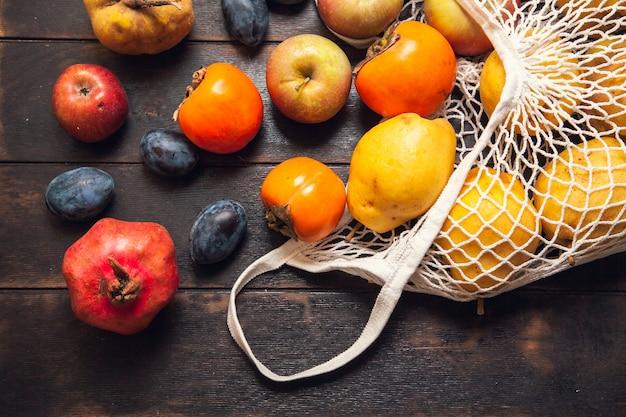 Verschiedene herbstfrüchte in einem netzbeutel auf einem dunklen hölzernen hintergrund.