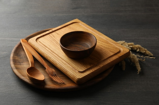 Verschiedene hölzerne küchenutensilien auf dunklem tisch