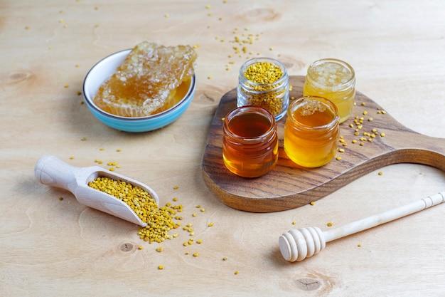 Verschiedene honigsorten in gläsern, waben und pollen