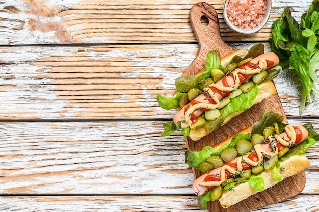 Verschiedene hot dogs mit gemüse, salat und gewürzen. weißer hölzerner hintergrund. draufsicht. speicherplatz kopieren.