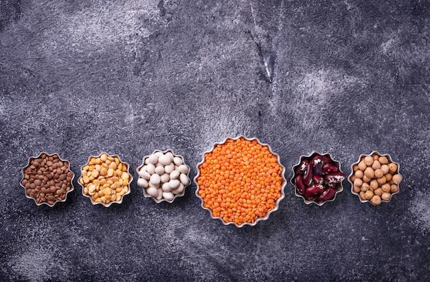 Verschiedene hülsenfrüchte. kichererbsen, rote linsen, schwarze linsen, gelbe erbsen und bohnen. selektiver fokus oben