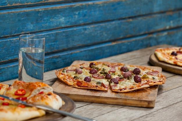 Verschiedene italienische pizza serviert mit glas wasser auf holzbrett