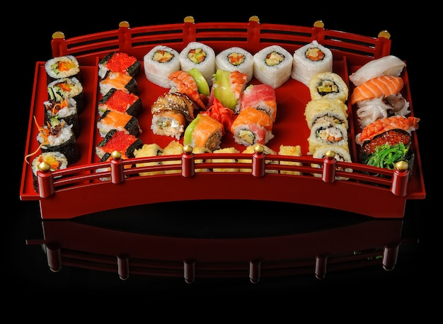 Verschiedene japanische sushi-sortimente serviert auf rotem tablett auf schwarzem