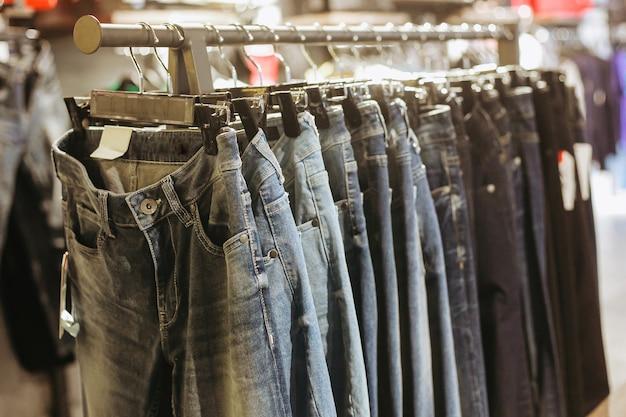 Verschiedene jeanshosen hängen an kleiderbügelkleidung im laden