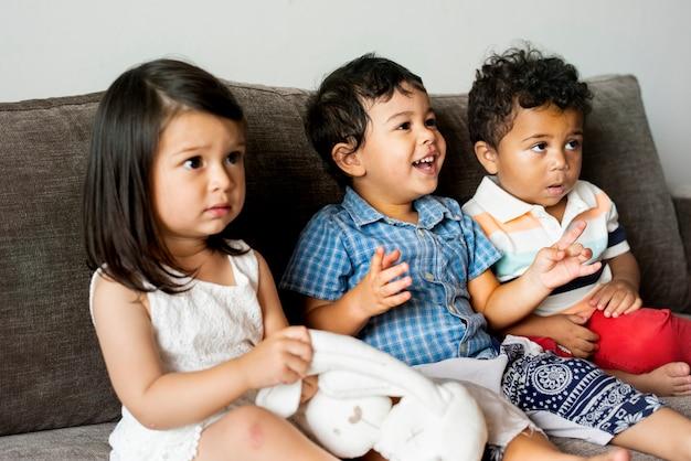 Verschiedene junge kinder, die zusammen auf der couch sitzen