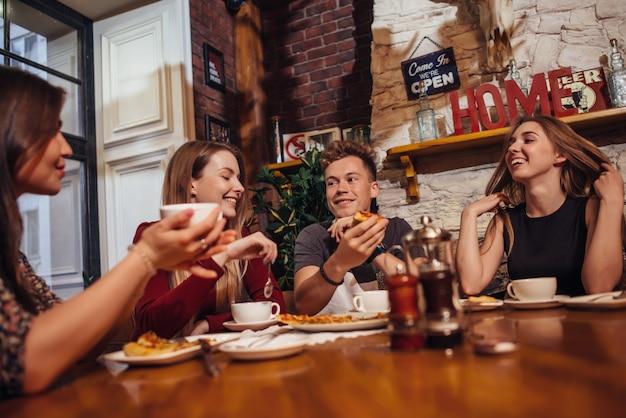 Verschiedene junge leute, die zu mittag plaudern und in einem café lächeln