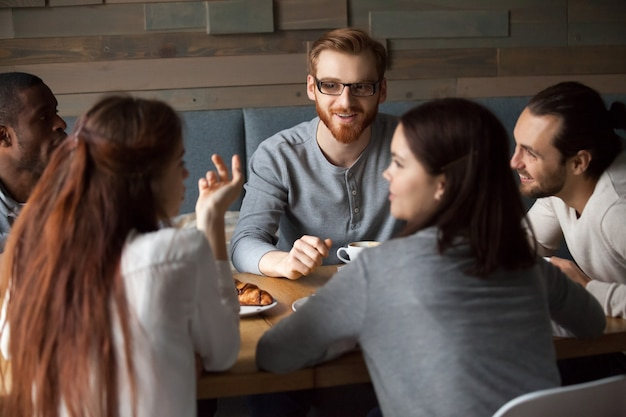 Verschiedene junge leute, die zusammen spaß im café sprechen und haben