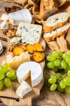 Verschiedene käse brie, camembert, roquefort, parmesan, blauschimmelkäse mit trauben, feigen, brot und nüssen. hölzerner hintergrund. draufsicht.