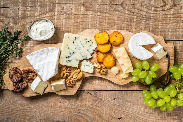 Verschiedene käse brie, camembert, roquefort, parmesan, blauschimmelkäse mit trauben, feigen, brot und nüssen.