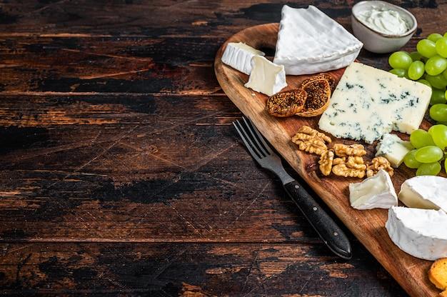 Verschiedene käsebretter mit brie, camembert, roquefort, parmesan, blauschimmelkäse, trauben und nüssen. dunkler hölzerner hintergrund. draufsicht. speicherplatz kopieren.