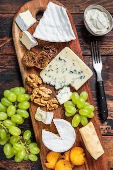 Verschiedene käsebretter mit brie, camembert, roquefort, parmesan, blauschimmelkäse, trauben und nüssen.