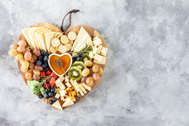 Verschiedene käsesorten auf einem hölzernen schneidebrett in form eines herzens. käse, trauben, walnüsse, oliven, rosmarin und ein glas weißwein. draufsicht, kopierraum
