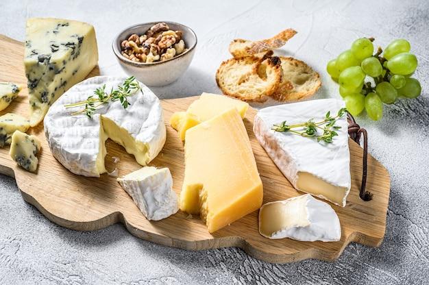 Verschiedene käsesorten auf einem holzschneidebrett