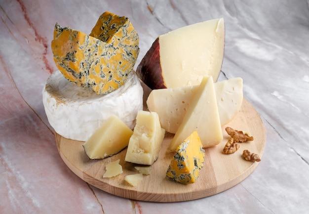 Verschiedene käsesorten auf einem holzteller
