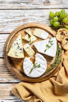 Verschiedene käsesorten auf einem runden holzschneidebrett